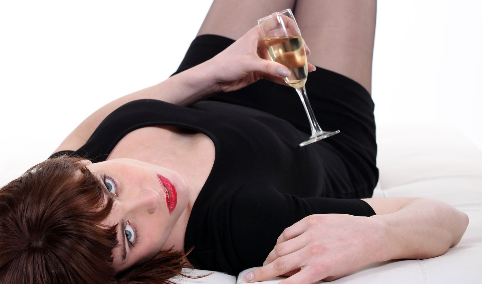 15224264 - drunk young woman lying in sofa with flute of champagne